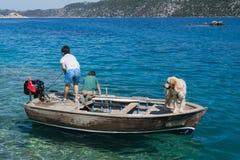 Twee jongens in boot en hond stock foto's