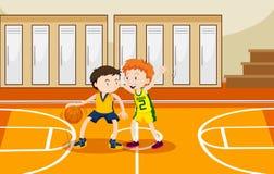 Twee jongens die basketbal in de gymnastiek spelen Stock Foto's