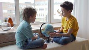 Twee jongens die de aardrijkskunde van de aarde met een bol bestuderen stock videobeelden