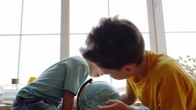 Twee jongens die de aardrijkskunde van de aarde met een bol bestuderen stock video