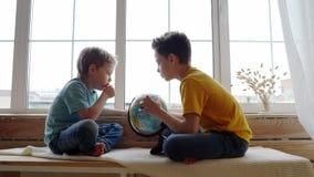 Twee jongens die de aardrijkskunde van de aarde met een bol bestuderen stock footage