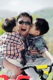 Twee jongens die de wangen van hun vader kussen stock afbeeldingen