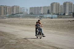 Twee jongens die een fiets berijden op strand in Sumgait, Azerbeidzjan Stock Foto