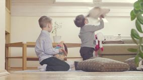 Twee jongens die gevulde speelgoed en kussens spelen stock footage