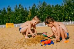Twee jongens die in het zand spelen stock foto