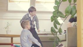 Twee jongens die kussens werpen bij iemand stock video