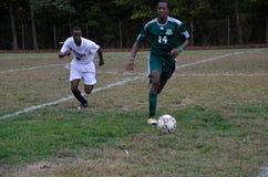 Twee jongens die middelbare schoolvoetbal spelen stock afbeeldingen