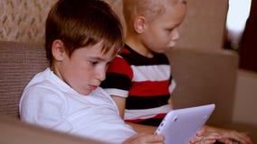 Twee jongens die op een tablet en laptop thuis spelen stock video