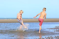 Twee jongens die op het strand spelen Royalty-vrije Stock Afbeeldingen
