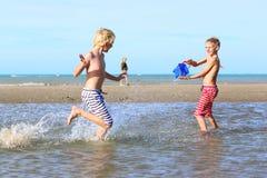 Twee jongens die op het strand spelen Stock Foto's