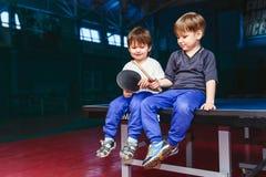 Twee jongens die op het tennis zitten dienen in Stock Foto