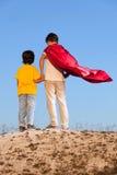Twee jongens die superheroes op de hemel spelen stock foto