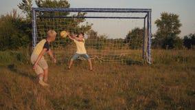 Twee jongens die voetbal spelen bij zonsondergang Een voetbalbal raakt Banner voor ontwerp Kinderen` s dromen van overwinningen stock footage