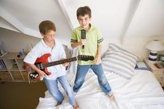 Twee Jongens die zich op het Spelen van het Bed bevinden stock foto's