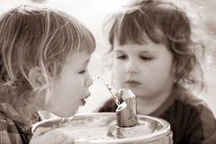Twee jongens door de het drinken fontein Stock Fotografie
