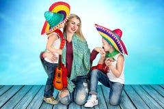 Twee jongens in een sombrero speelt de gitaar en zingt een serenade voor zijn moeder stock afbeelding
