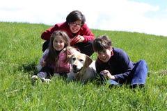 Twee jongens en een meisje met Labradorhond Royalty-vrije Stock Afbeeldingen