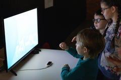 Twee jongens en een meisje spelen een 3D virtuele werkelijkheid Stock Afbeeldingen