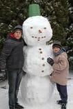 Twee jongens en een sneeuwman stock foto's