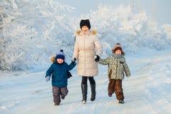 Twee jongens en grootmoeder in het de winterbos Stock Afbeeldingen