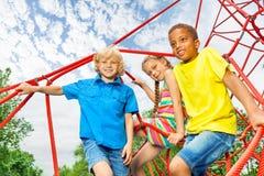 Twee jongens en het meisje zitten op rode kabels van speelplaats Stock Foto