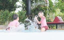 Twee jongens genieten van bespattend water in de pool royalty-vrije stock afbeeldingen
