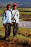 Twee jongens op de manier aan school door de padievelden Stock Afbeelding