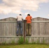 Twee jongens op de omheining die smth zoekt Stock Afbeeldingen