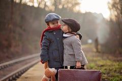 Twee jongens op een station, die op de trein wachten Stock Afbeeldingen