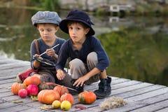 Twee jongens schilderen kleine Halloween-pompoenen Stock Fotografie