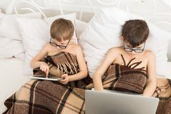 Twee jongens spelen bij laptop en tablet met hond in bed Royalty-vrije Stock Afbeelding