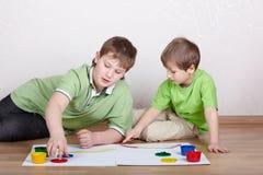 Twee jongens trekken verven op bladen van document Stock Foto