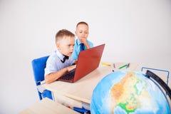 Twee jongens zitten op de computertrainingsschool stock afbeelding