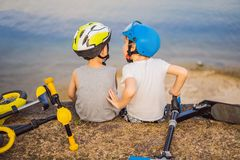 Twee jongens zitten op de kust van het meer na het berijden van een fiets en een autoped royalty-vrije stock foto's