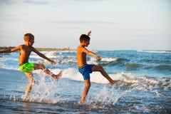 Twee jongensadolescentie het spelen in de zeewater bespattende voeten wat royalty-vrije stock foto