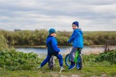 Twee jongenskleuter die op fietsen de camera bekijken stock afbeelding