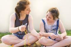 Twee jongeren die armbanden maken royalty-vrije stock afbeeldingen