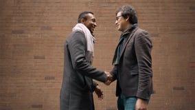 Twee jongeren die in de straat en het schudden handen samenkomen