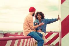 Twee jongeren die en emotioneel gesprek hebben lachen stock afbeeldingen