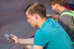 Twee jongeren die het scherm in smartphone bekijken stock afbeeldingen