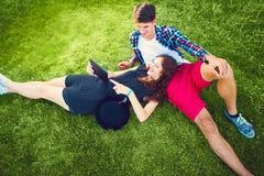 Twee jongeren die op het gras genieten van stock foto