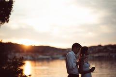 Twee jongeren die van een glas rode wijn in de zonsondergang op de kust genieten Gezonde glasod eigengemaakte rode Mediterrane wi Royalty-vrije Stock Foto's