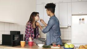 Twee jongeren die van hun tijd genieten die samen, lunch in keuken op z'n gemak maken Samen het leven De mulatkerel voedt stock videobeelden