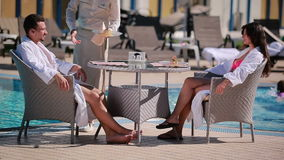 Twee jongeren die in witte badjassen dichtbij het zwembad zitten stock videobeelden