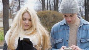 Twee jongeren, een mooi blonde en haar vriend, loopt onderaan de straat en gebruikt mobiele telefoons Schrijf berichten stock footage