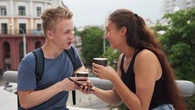 Twee jongeren, het drinken koffie die en het gebruiken van smartphone in stad spreken stock footage
