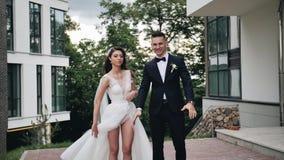 Twee jonggehuwden het meisje maakt haar kleding recht en de kerel toont iets aan de camera stock videobeelden