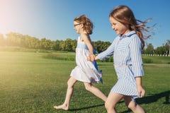 Twee joyfullmeisjes die op het gebied lopen Stock Foto