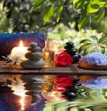 Twee kaarsen en handdoeken zwart-witte stenen en amandelbloesem op water Royalty-vrije Stock Fotografie