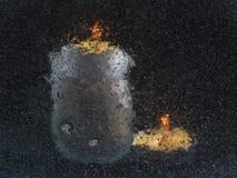 Twee kaarsen, schot door een glas met luchtbellen: vage silhouetten van kaarsen op een zwarte achtergrond Stock Foto's